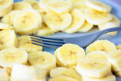 Slices of banana on light blue plate with fork Royalty Free Stock Image