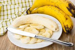 Slices of bananas in plate and knife on table Stock Image