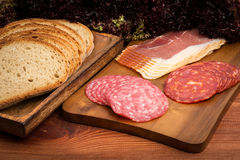 Slices of  becon and salami on the brown wooden board. Slices of  becon and salami on the wooden board Stock Photography