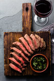 Slices of beef medium rare steak on wooden board, glass of red wine Royalty Free Stock Image