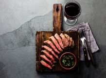 Slices of beef medium rare steak on wooden board, glass of red wine. On slate background stock images