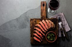 Slices of beef medium rare steak on wooden board, glass of red wine. On slate background royalty free stock image