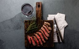 Slices of beef medium rare steak on wooden board, glass of red wine. On slate background stock photos