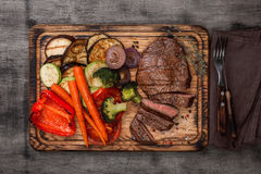 Slices of beef steak with grilled vegetables on cutting board Stock Images