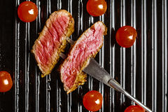 Slices of beef steak on meat fork and cherry tomatoes. Beef steak on the grill pan with spices and tomatoes Royalty Free Stock Image
