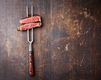 Slices of beef steak on meat fork. On dark wooden background royalty free stock image
