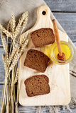 Slices of black Bread, honey and wheat spikelets Stock Image