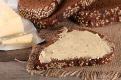 Slices of black bread with sesame seeds and butter on an old wooden background.  Stock Image