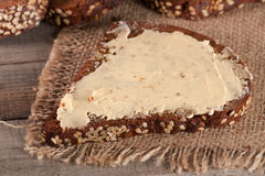 Slices of black bread with sesame seeds and butter on the old wooden background.  Stock Photos