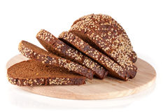 Slices of black bread with sesame seeds on a cutting board isolated on white background.  Royalty Free Stock Images