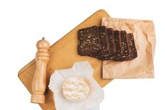 Slices of black rye bread with sunflower seeds lie on a wooden board next to the cheese near the knife. Time for bite Stock Photo