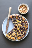 Slices of blueberry tart on a blue plate and roasted almonds.Top view Royalty Free Stock Photos