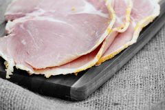 Slices of boiled ham on a wooden chopping board. Royalty Free Stock Images