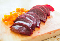 Slices of boiled red beat and carrots on a wooden board Royalty Free Stock Image