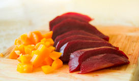Slices of boiled red beat and carrots on a wooden board Royalty Free Stock Photography