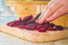 Slices of boiled red beat on a wooden board and a hand Stock Image