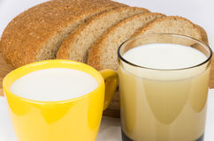 Slices of bran bread, glass and cup of milk Stock Photos