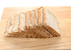 Slices of bran bread on wooden board isolated on white backgroun. Slices of homemade bran bread on wooden board isolated on white background stock photo