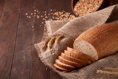 Slices of bread on burlap on the wooden table. composition with wheat ears scattered around and ears of wheat. Stock Images