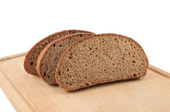 The slices bread on a chopping board. The cut bread on a chopping board on a white background Royalty Free Stock Photos