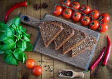 Slices of bread on a cutting Board, fresh tomatoes, fragrant Basil and hot pepper on a wooden table. stock image