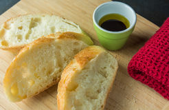 Slices of bread on cutting board with oil and cloth Stock Image