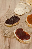 Slices of bread with different tipes of jam. On wood background Stock Images