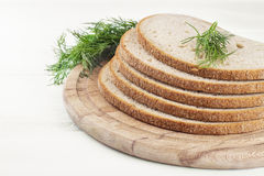 Slices of bread with dill on a cutting wooden board. Slices of bread with dill on a cutting board Royalty Free Stock Images