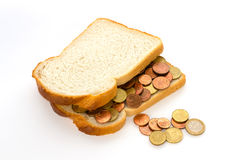 Slices of bread with euro coins spread. Slices of white bread with euro coins spread and some spilling Royalty Free Stock Photo