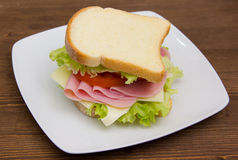 Slices of bread with ham and salad on wood Royalty Free Stock Photo