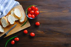 Slices of bread, loaf or baguette on a wooden cutting Board, table. Near ripe tomatoes in a Cup, a towel, a knife. Cooking organic royalty free stock photo