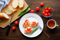 Slices of bread, a mug of tea, sandwiches with cheese and tomatoes, green salad sheets on a wooden table. The concept of organic. Farm products for Breakfast or royalty free stock photography