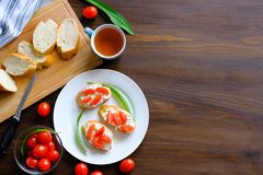Slices of bread, a mug of tea, sandwiches with cheese and tomatoes, green salad sheets on a wooden table. The concept of organic. Farm products for Breakfast or royalty free stock photo