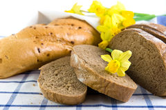 Slices of bread and narcissuses on a napkin. Slices of bread and yellow narcissuses on a checkered napkin Royalty Free Stock Photos