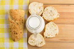 Slices of bread, pieces of baguette and jug milk Stock Images