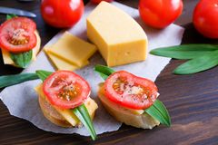 Slices of bread, sandwiches, red tomatoes, sliced cheese, greens on a wooden table. The concept of organic farm products, cooking stock photography
