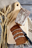Slices of bread, wheat spikelets and knife on a cutting board Royalty Free Stock Images