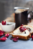 Slices of butter poppy roll, served with cherry jam and large ceramic cup with hot drink. Royalty Free Stock Image