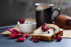 Slices of butter poppy roll, served with cherry jam and large ceramic cup with hot drink. Royalty Free Stock Photos