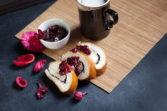 Slices of butter poppy roll, served with cherry jam and large ceramic cup with hot drink. Royalty Free Stock Photography