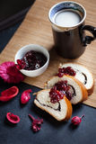 Slices of butter poppy roll, served with cherry jam and large ceramic cup with hot drink. Stock Photo