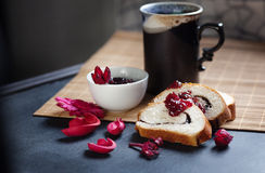 Slices of butter poppy roll, served with cherry jam and large ceramic cup with hot drink. Stock Photography
