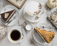 Slices of cake with caramel and chocolate, fresh coffee, milk, vintage spoons, frame, book, pumpkin and meringue. stock photos