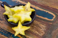 Slices of carambola in black bowl. Slices of carambola fruit in black bowl on wooden table Royalty Free Stock Photo