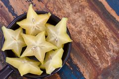 Slices of carambola fruit on black plate Stock Photos