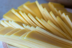 Slices of chees on a plate. Many slices of yellow cheese on a plate Royalty Free Stock Photo