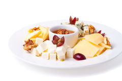 Slices of cheese. A plate with slices of cheese of different varieties on a white background with nuts and honey Royalty Free Stock Photo
