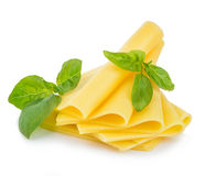 Slices of cheese with fresh basil leaves close-up isolated on white background. Royalty Free Stock Images
