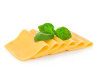 Slices of cheese with fresh basil leaves close-up isolated on a white background. Stock Photos