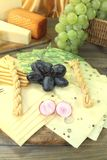 Slices of cheese with grapes and radisches Stock Images